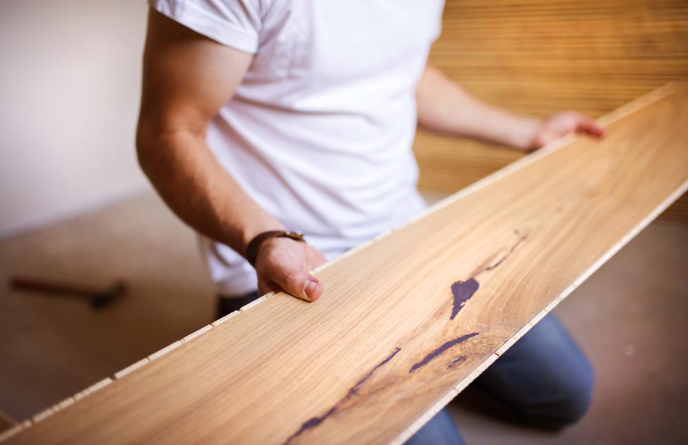 Φωτό handyman installing wooden floor PZLDP3K