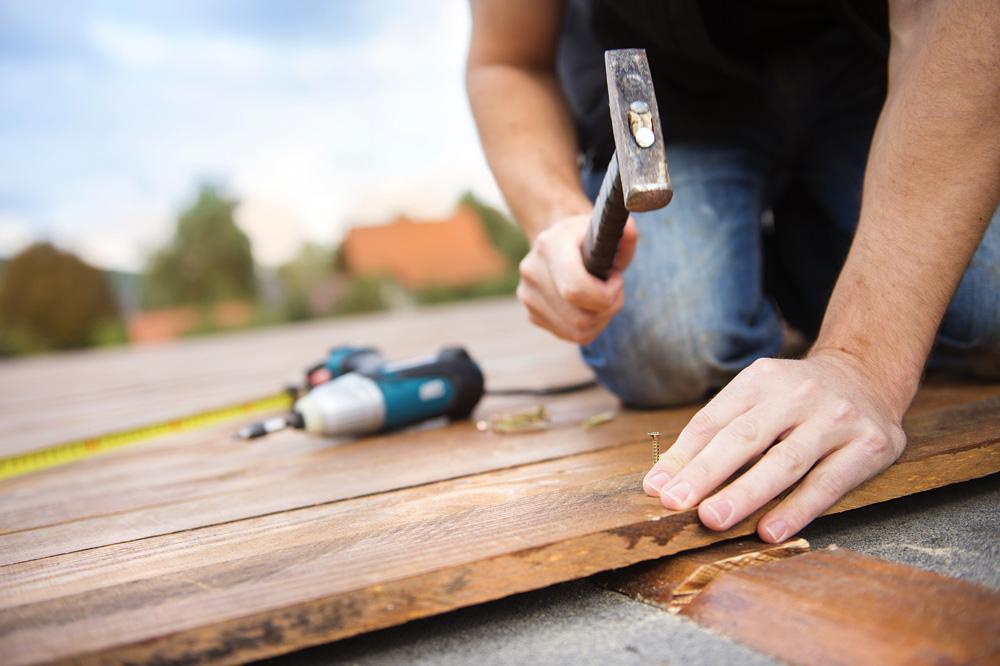 Φωτό handyman installing wooden flooring PKEZESQ