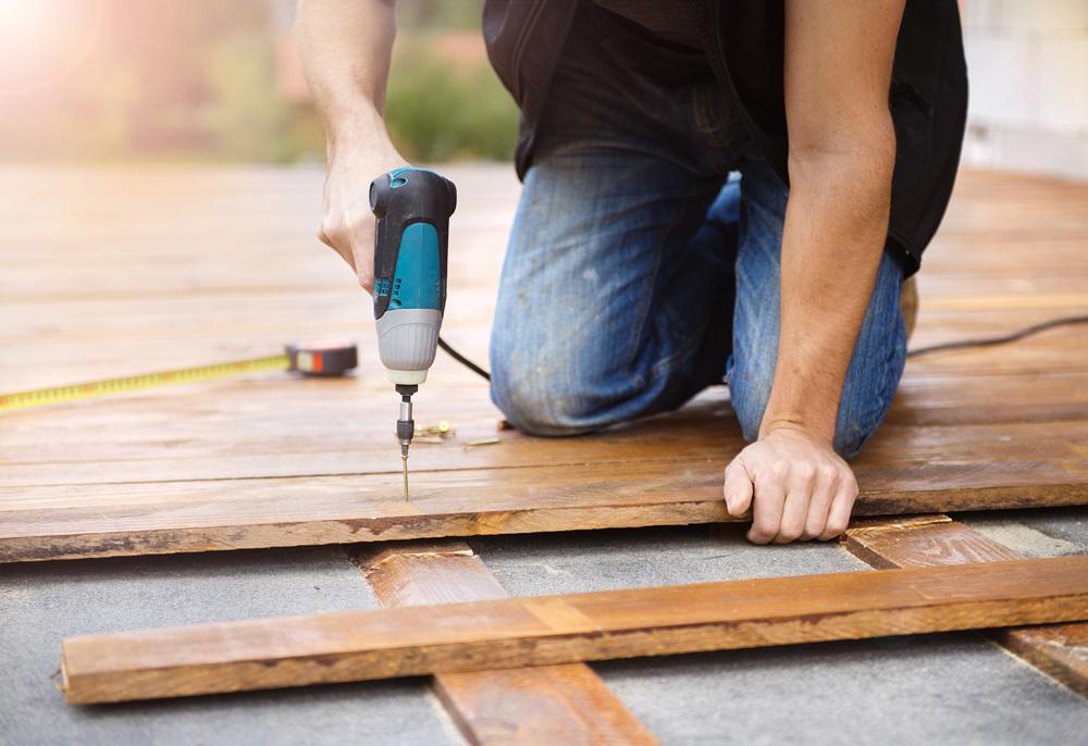 Φωτό handyman installing wooden flooring PVGJLXK