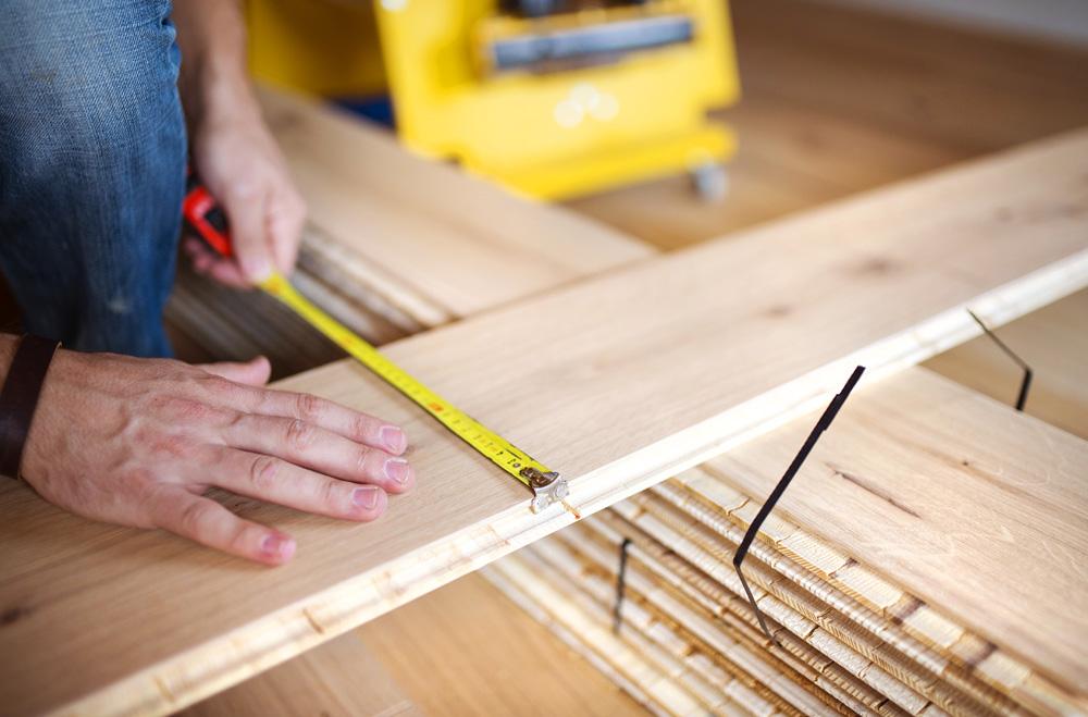 Φωτό handyman measuring wooden floor PCZ78FH