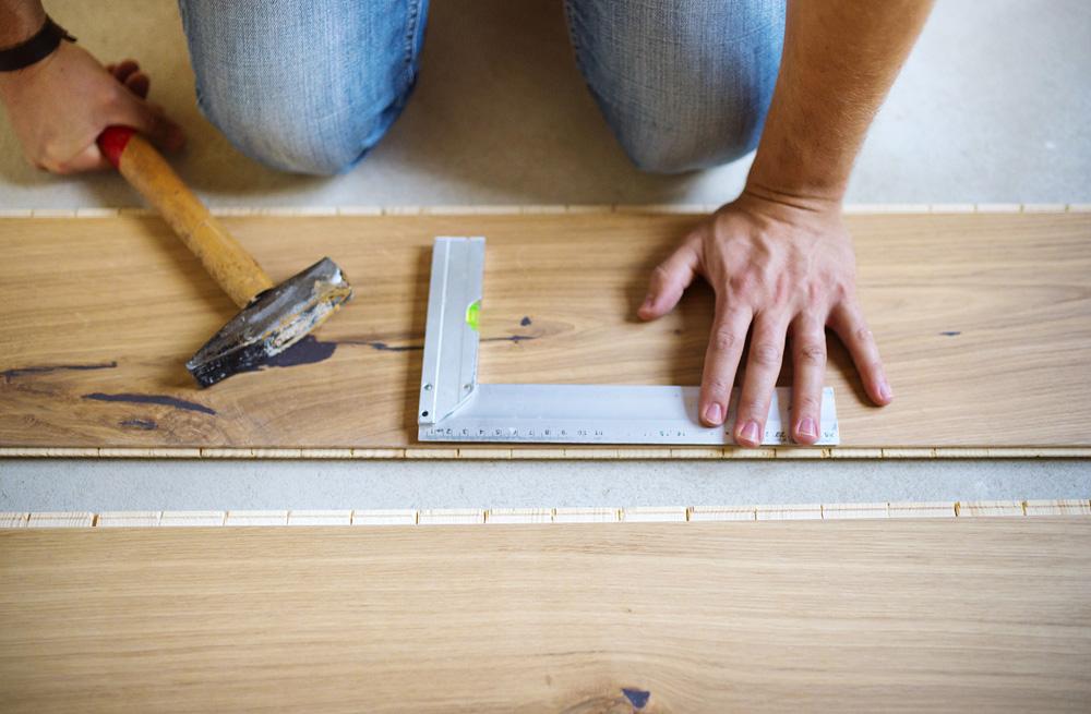 Φωτό handyman measuring wooden floor PV6AUAZ